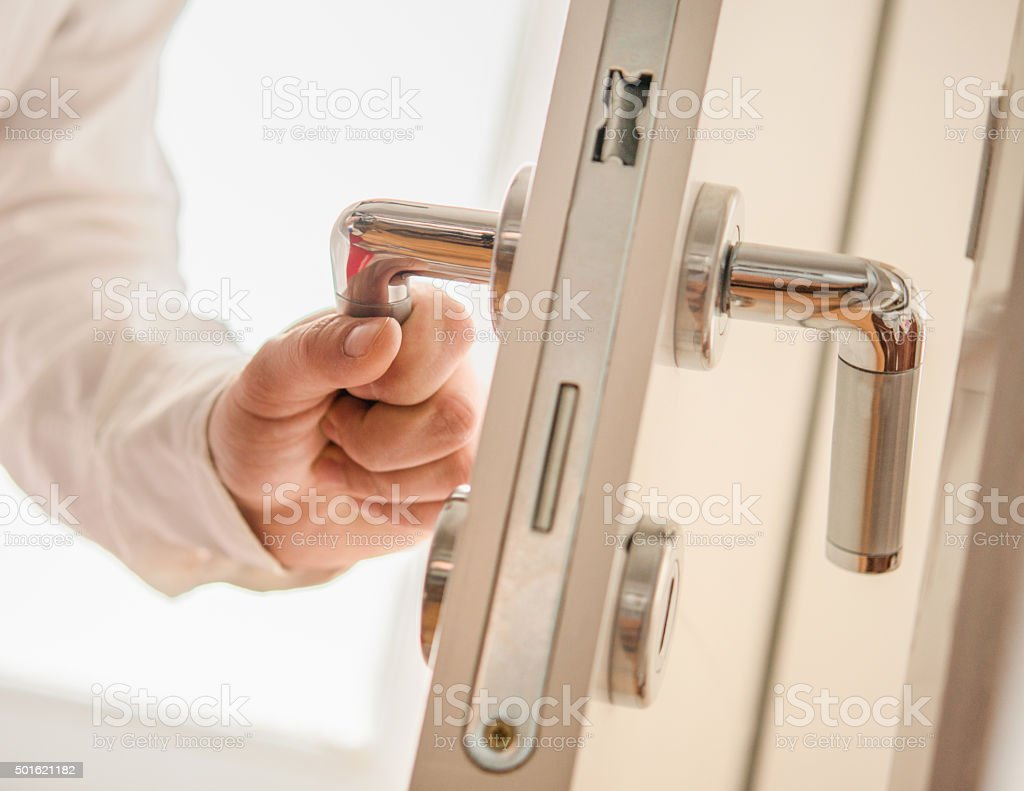 Hand opens the door stock photo