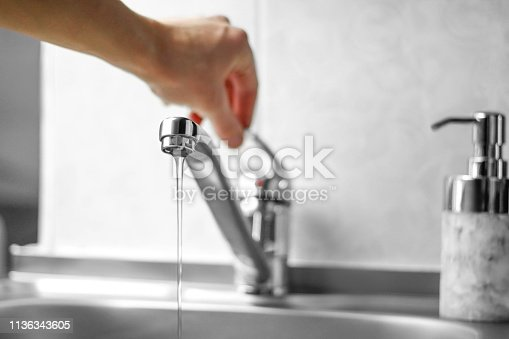 Hand opens the water tap. Close up.