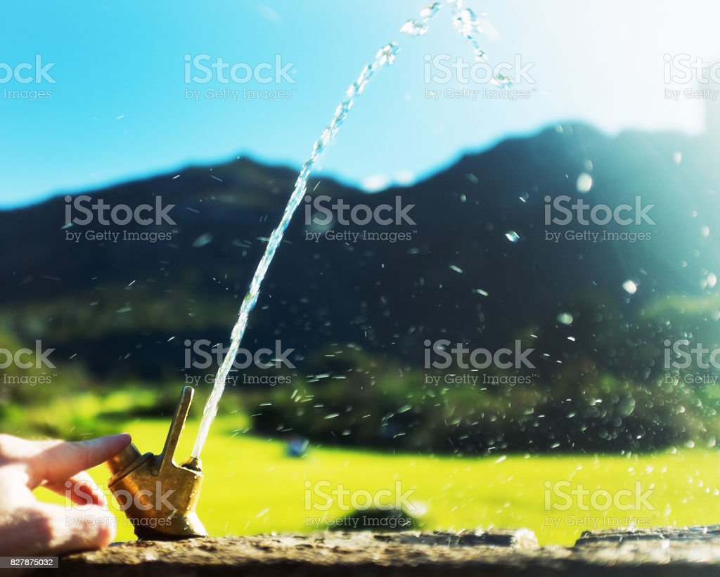 Hand operating drinking fountain in beautiful park setting stock photo