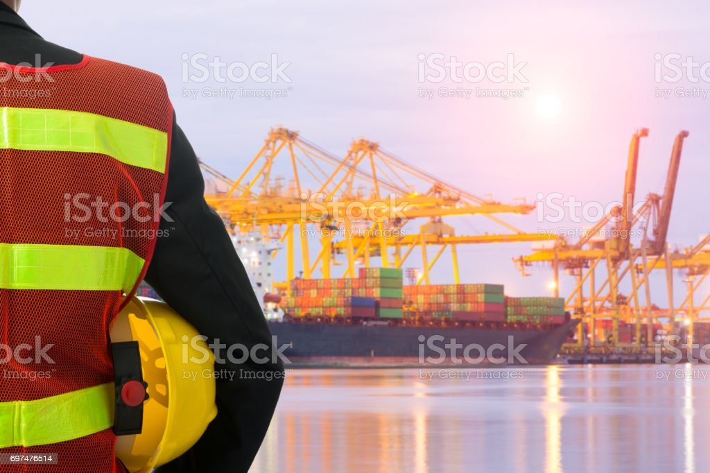 Hand or arm of engineer hold yellow plastic helmet in front of cargo stock photo