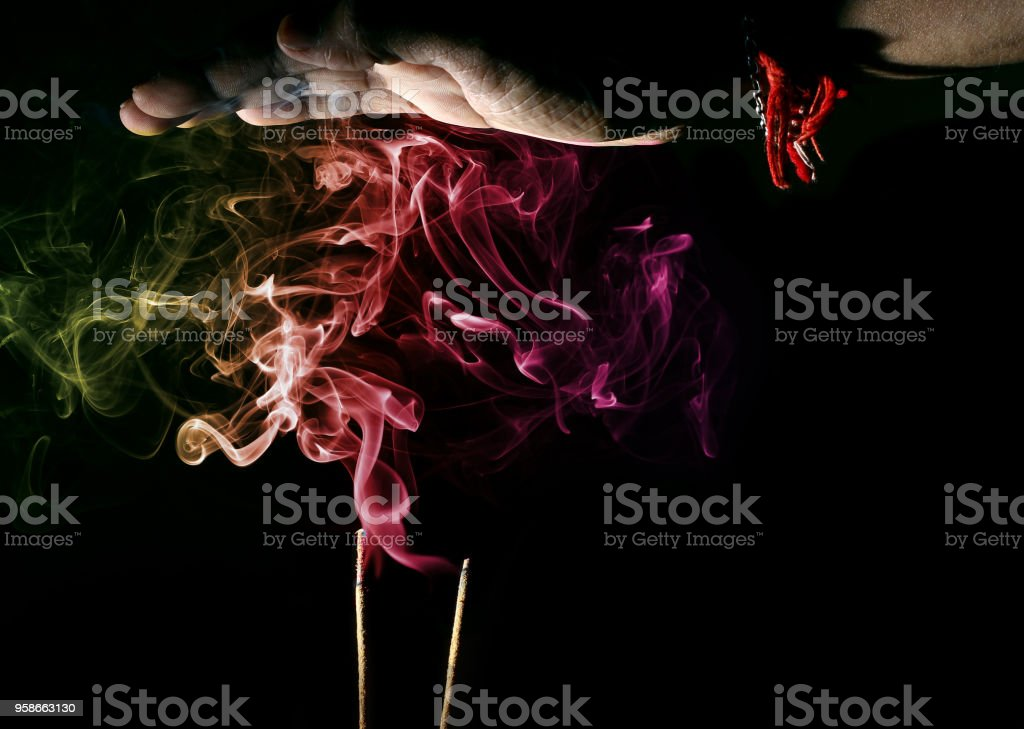 hand over smoke from an incense stick for divine religious blessings stock photo