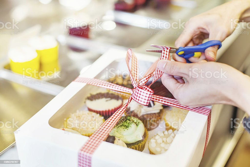 Hand packing many kinds of cupcakes a stock photo