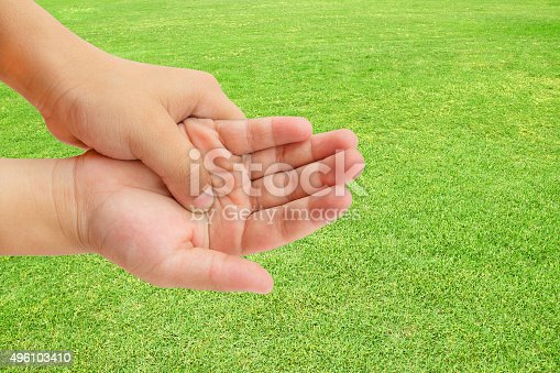 istock hand pain on green grass background 496103410