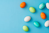 Hand painted colourful easter eggs on blue background. Directly above table top shot.