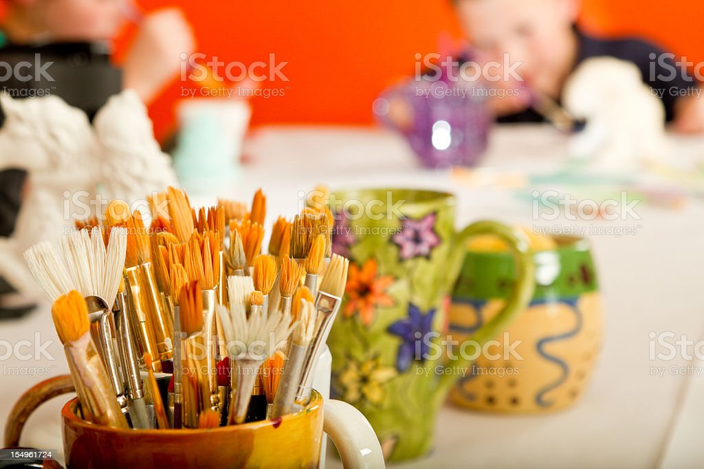 Hand painted Cup Full of Paintbrushes stock photo
