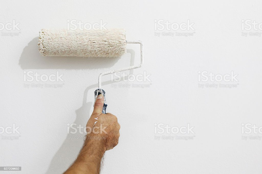 hand painter man at work with paint roller, wall painting stock photo