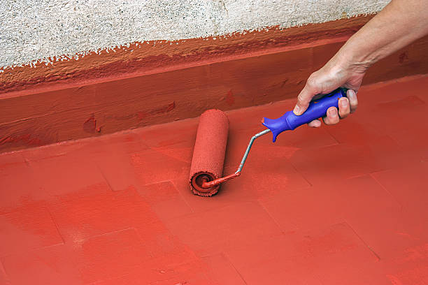 Hand painting a red floor with a paint roller Hand painting a red floor with a paint roller for waterproofing waterproof stock pictures, royalty-free photos & images