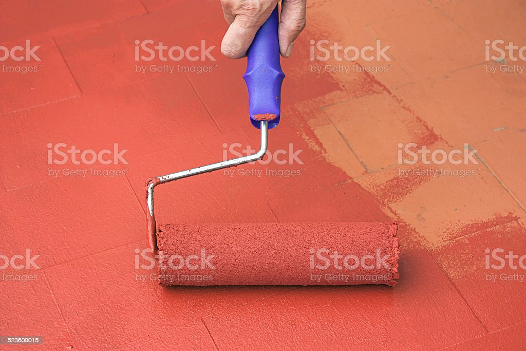 Hand painting a red floor with a paint roller stock photo