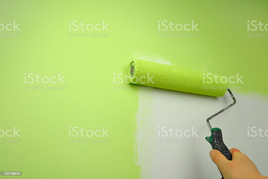 Hand painting a wall in green paint using a roller stock photo