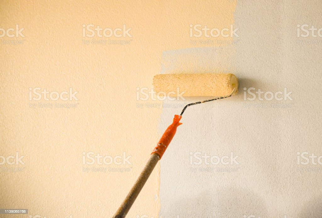Hand painting wall background with paint roller on building...