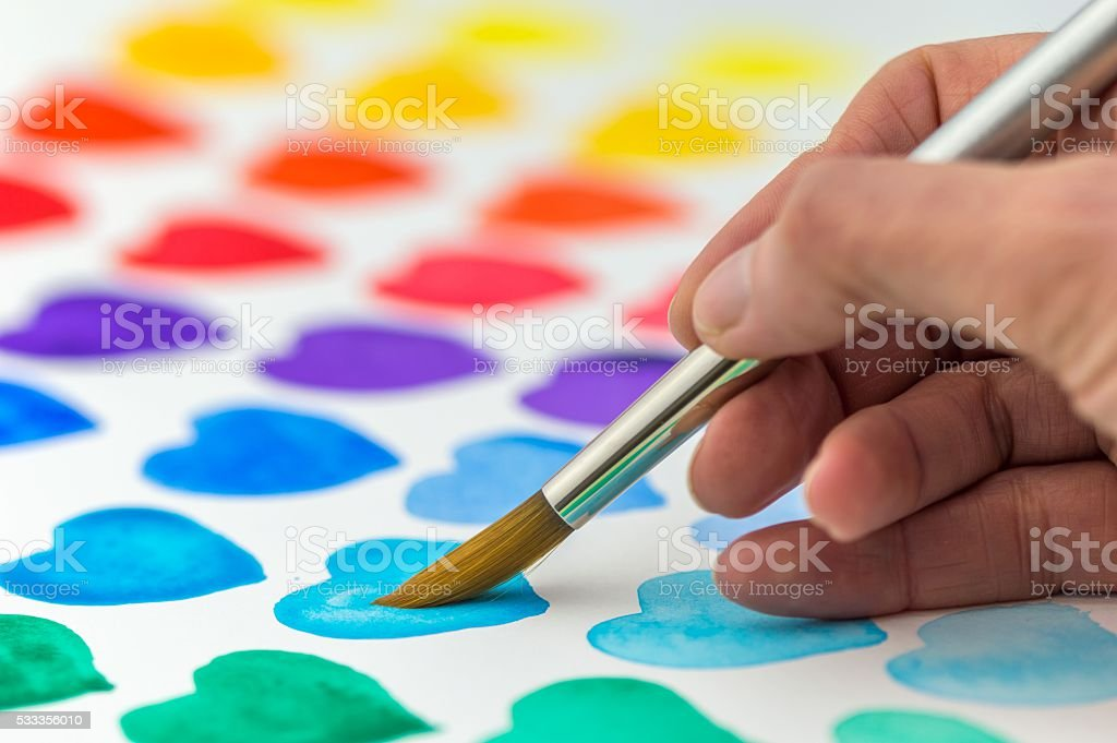 Hand painting watercolor hearts with a paintbrush. stock photo