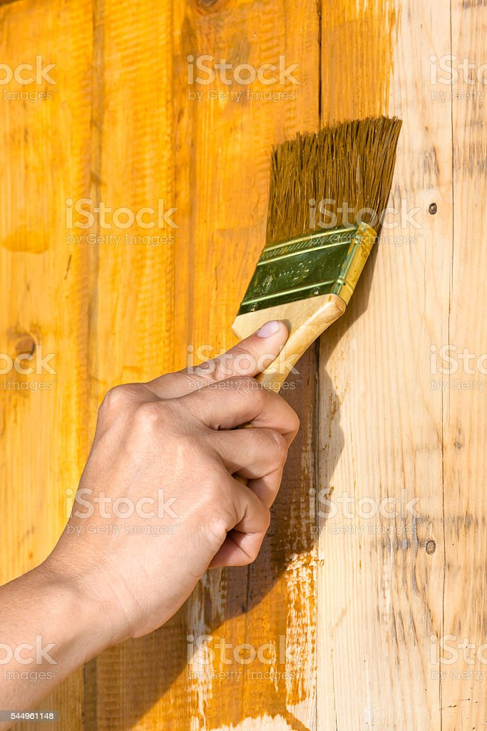 hand painting wood boards with brush stock photo