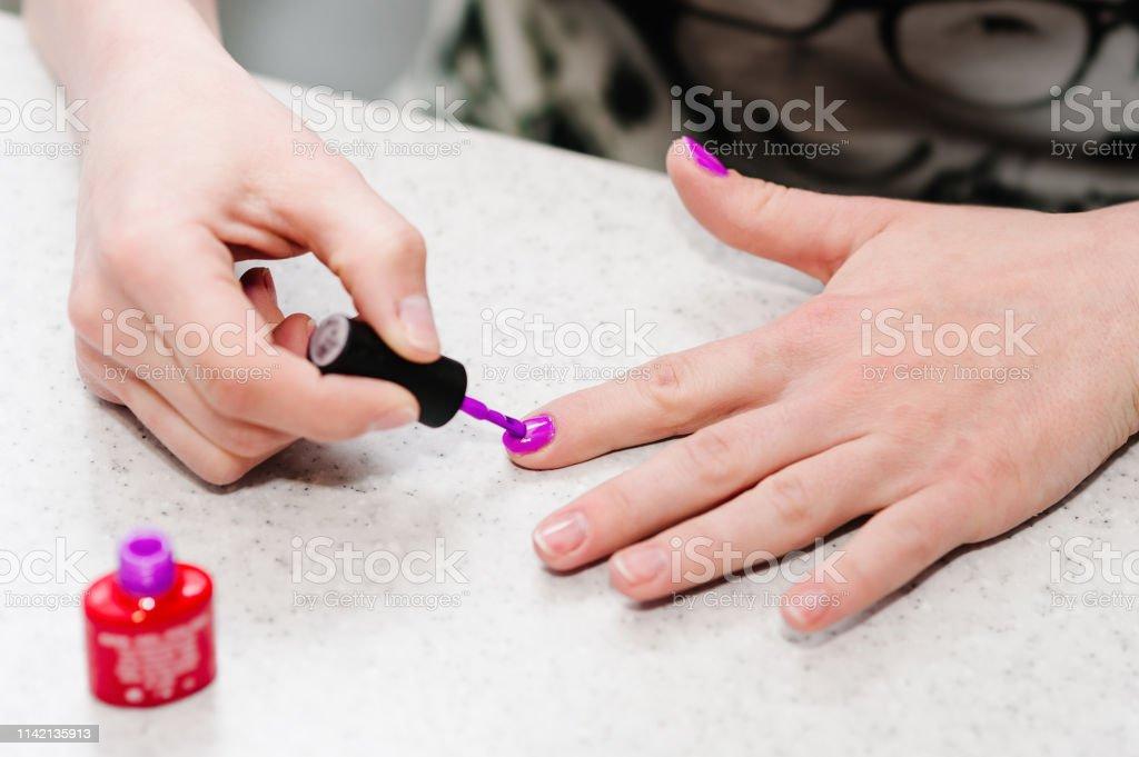 Hand paints the nails, gel purple, gel nail manicure.