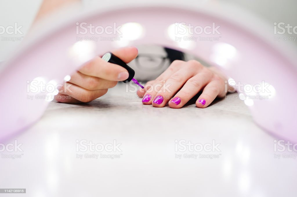 Hand paints the nails, gel purple, gel nail manicure through the lamp...