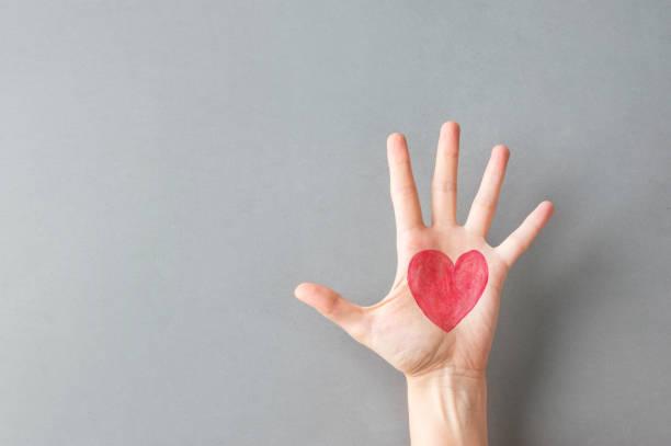 Handfläche von jungen kaukasischen Frau Mädchen mit auf rotem Herzen auf grauen Wandhintergrund gemalt. Charity Liebe Spende Valentine Gesundheitskonzept. Kreatives Social-Plakat-Banner mit Kopierraum – Foto
