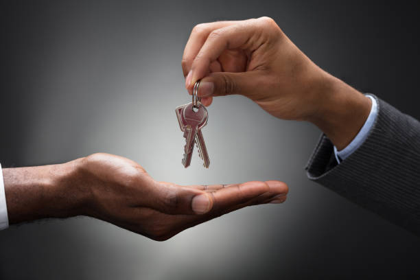 hand passing keys to new owner - key stock pictures, royalty-free photos & images