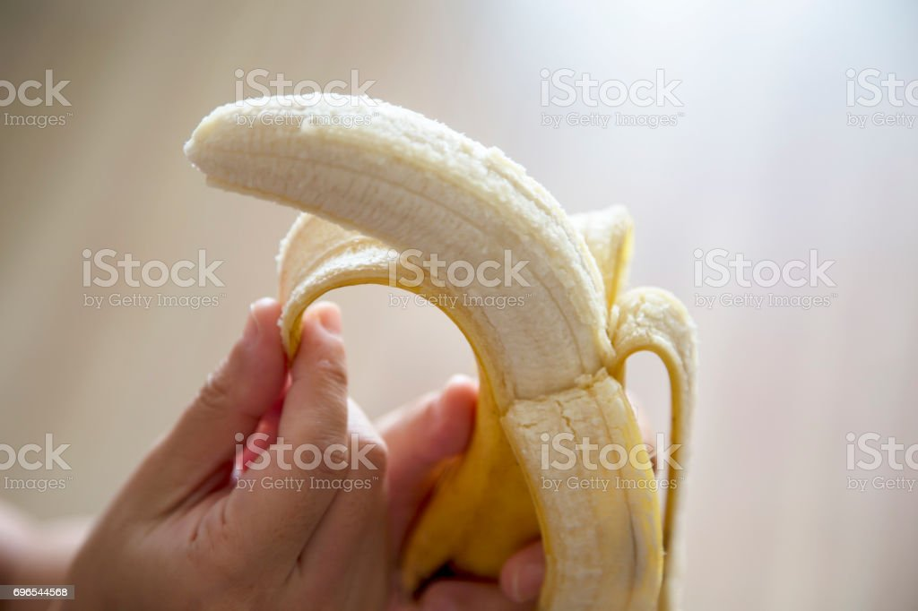 hand peeling banana stock photo