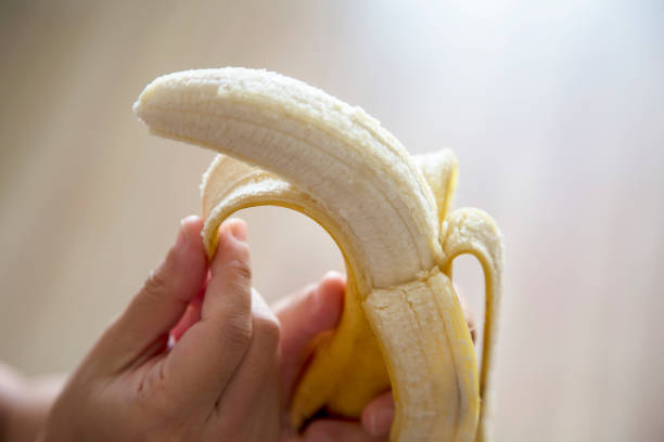 hand peeling banana - peeled stock photos and pictures