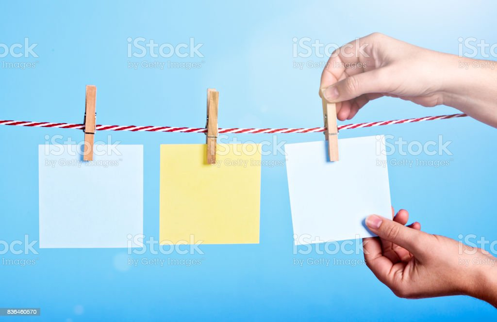 Hand pegging blank notes to sunlit washing line stock photo