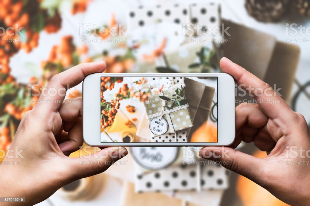 Hand taking photo with smart phone. Christmas gift box stack with...