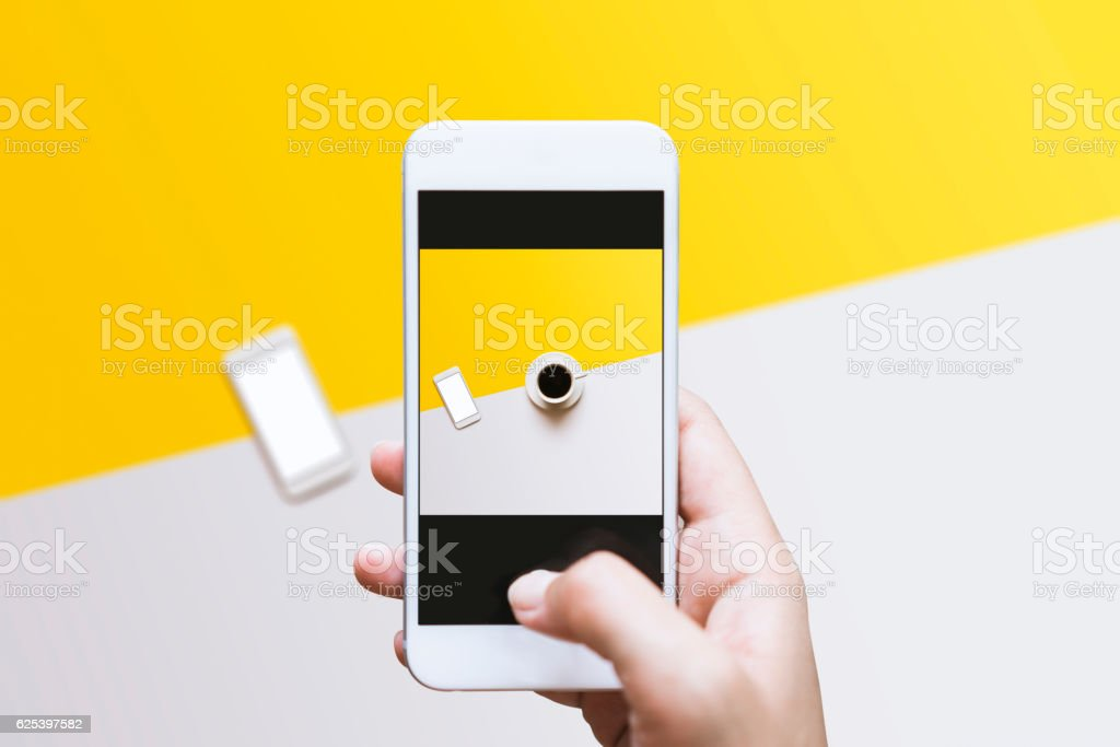 Hand photographing food on color block background with mobile phone stock photo