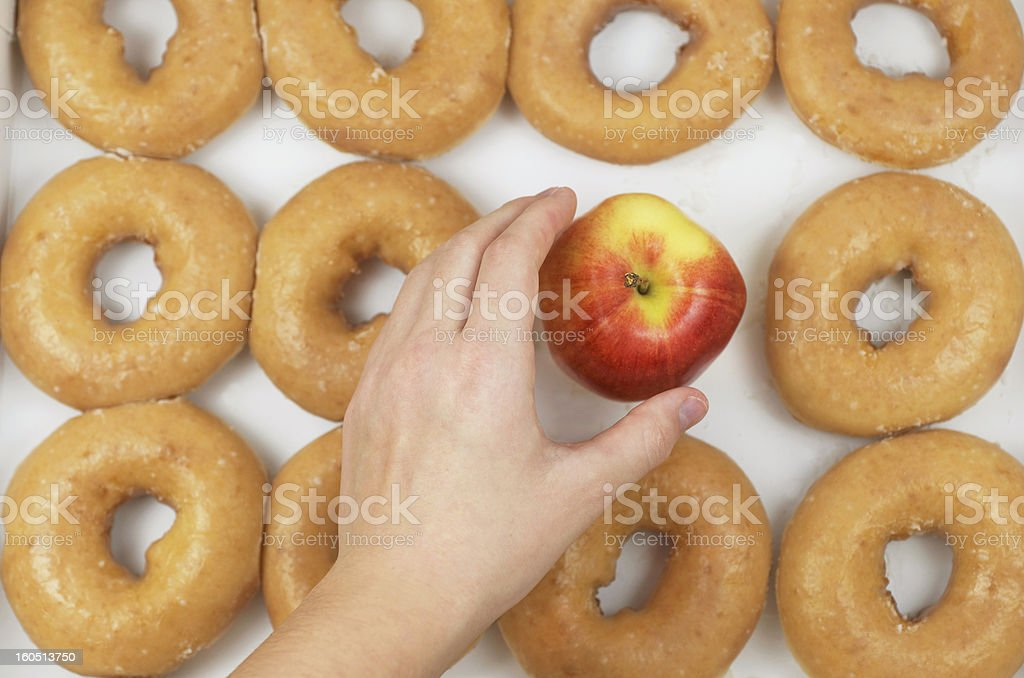 Hand Picking Apple From A Dozen Donuts royalty-free stock photo