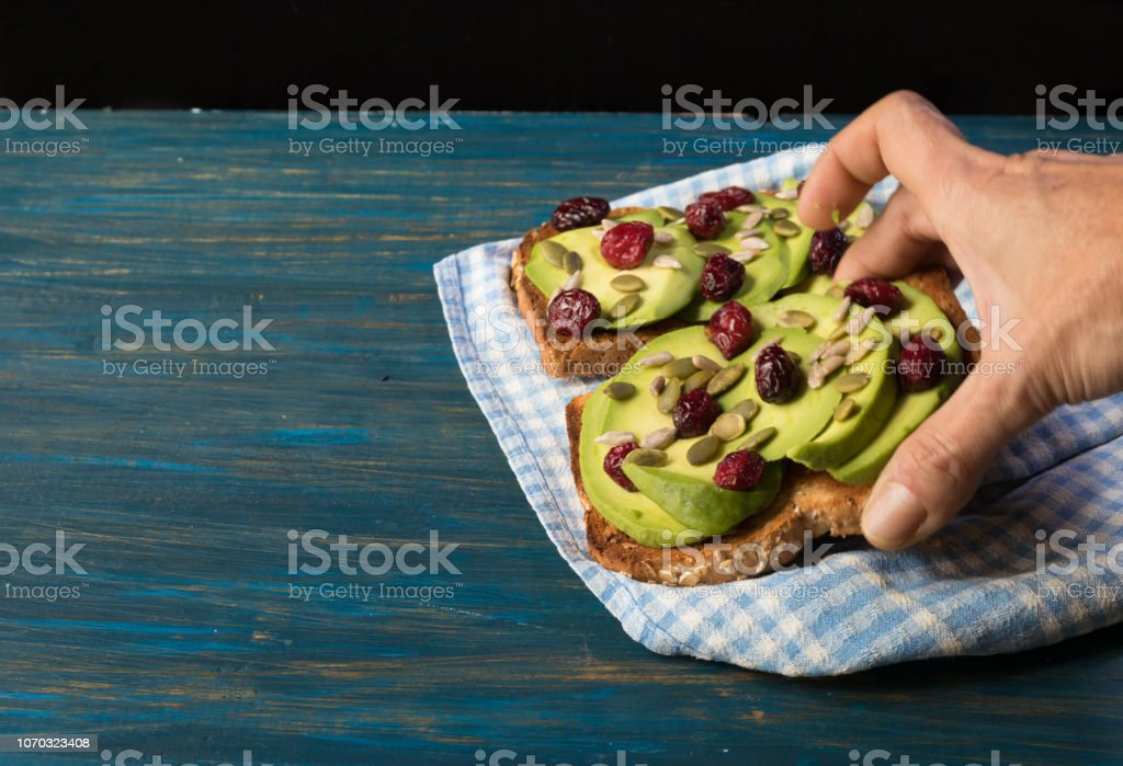 Hand picking avocado toast with blueberries and pips stock photo