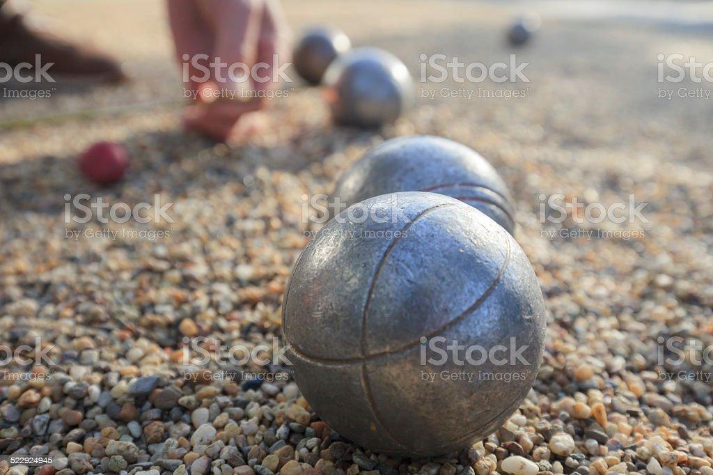hand picking up a metallic petanque ball stock photo