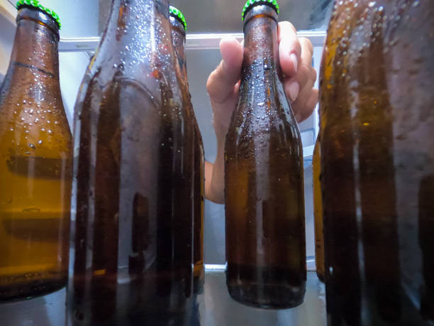 A hand picking up an ice cold beer bottle from the fridge stock photo