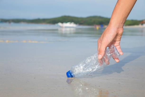 main à ramasser une bouteille en plastique de nettoyage sur la plage». campagne pour nettoyer. sauver le monde - recyclage main photos et images de collection