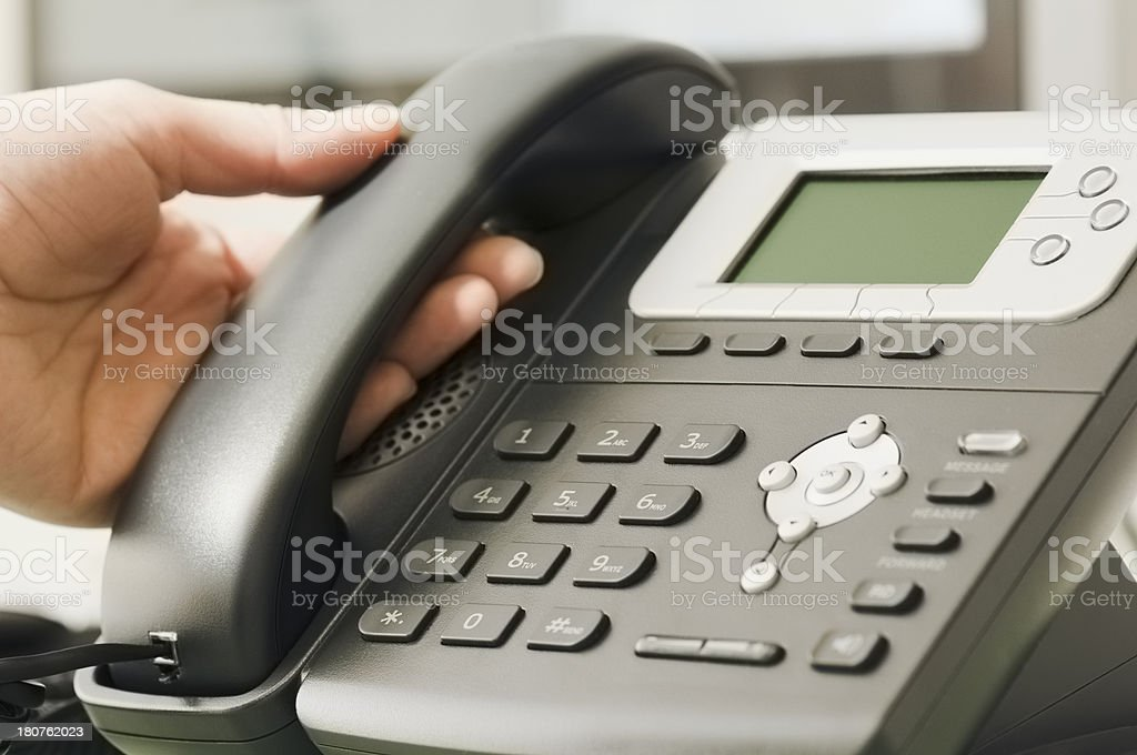 Hand picking up receiver of business telephone royalty-free stock photo