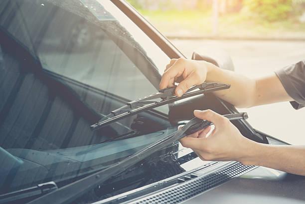 hand picking up windscreen wiper - voorruit stockfoto's en -beelden
