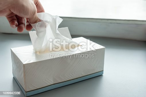Hand picking white tissue paper from package box
