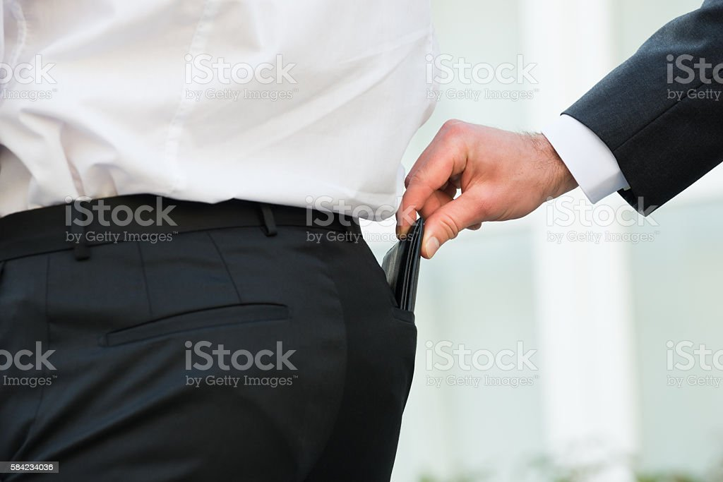 Hand Pickpocketing Wallet Of Businessman stock photo