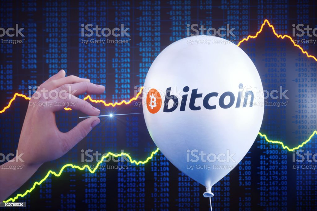 Hand piercing Bitcoin bubble with stock data stock photo