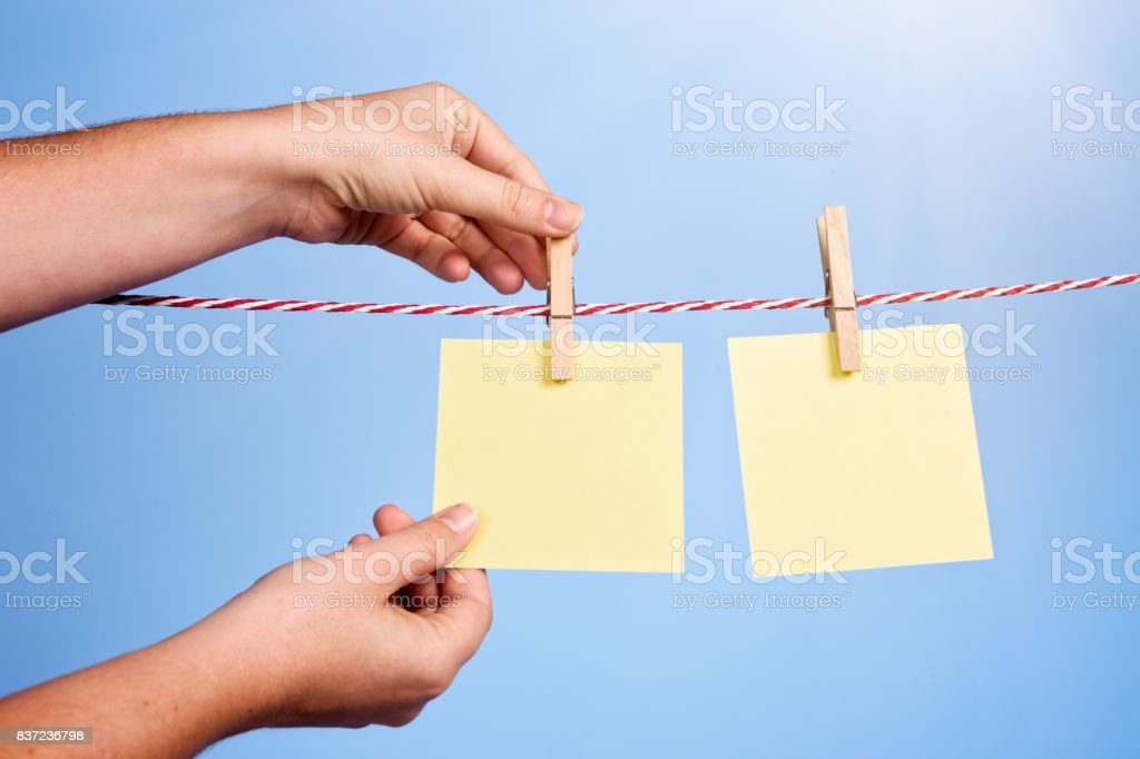 Hand pinning blank yellow messages to sunlit washing line stock photo