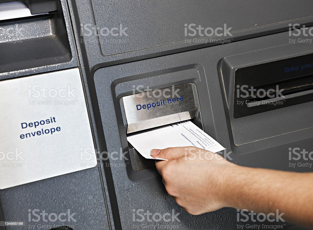Hand places deposit envelope in  ATM slot stock photo