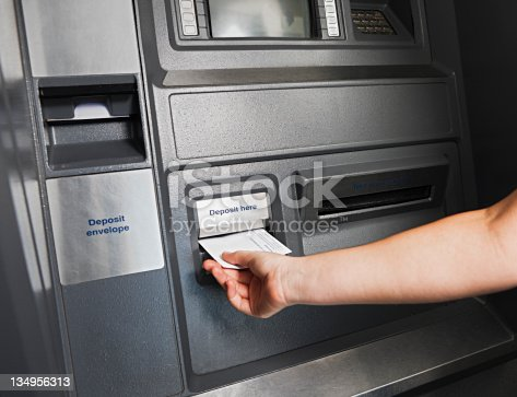 At the automatic teller machine, a woman's hand puts an envelope into the slot marked for deposits. Shot with Canon EOS 1Ds Mark III.