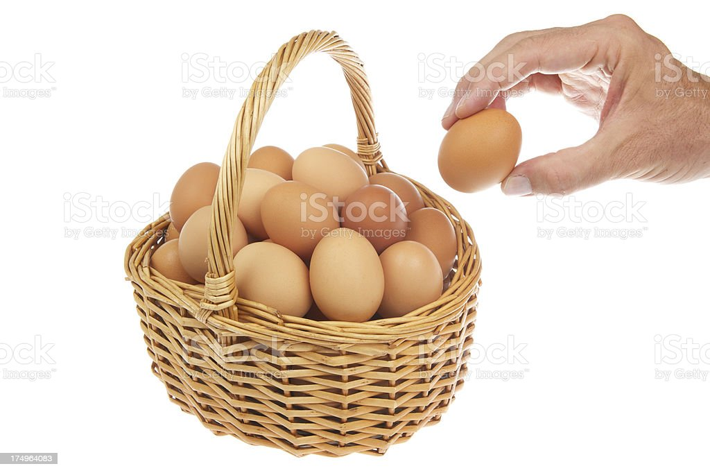 Hand Places Egg to Add All Eggs in One Basket stock photo