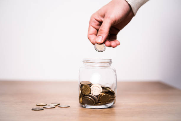 Hand placing a coin in a jar stock photo