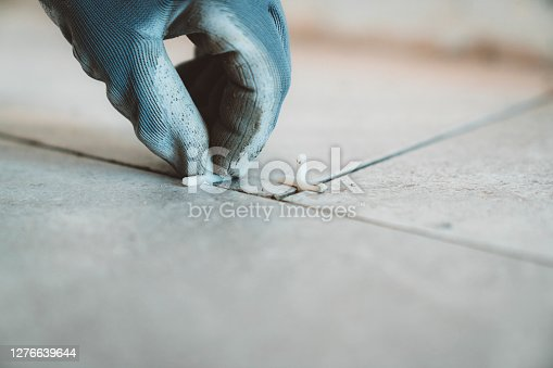 Hand holding a spacer placing it between the tiles. Close up.