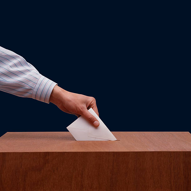 Hand placing ballot paper into wooden box stock photo