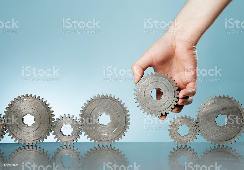 Hand placing gear in a row of other gears on a background royalty-free stock photo