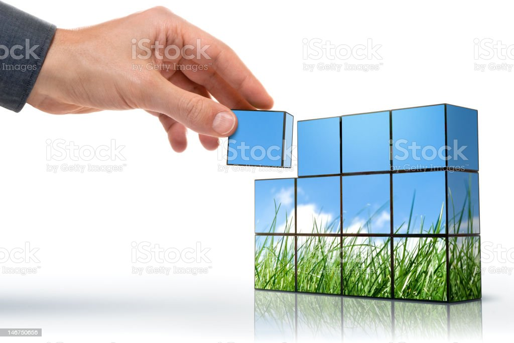 A hand placing the final cube to complete a picture stock photo