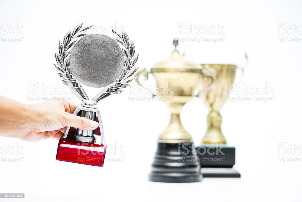 Hand placing trophy beside other awards royalty-free stock photo