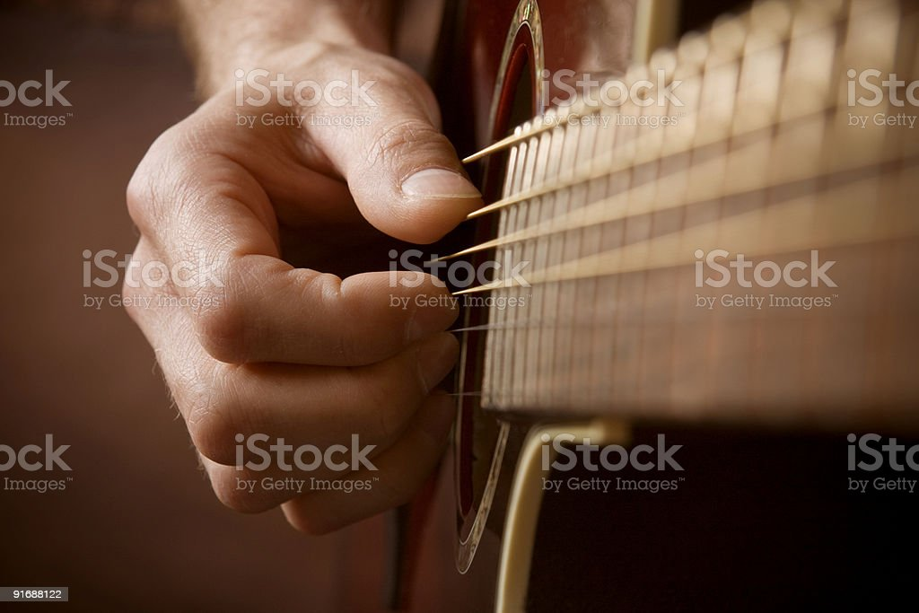 Hand playing acoustic guitar stock photo