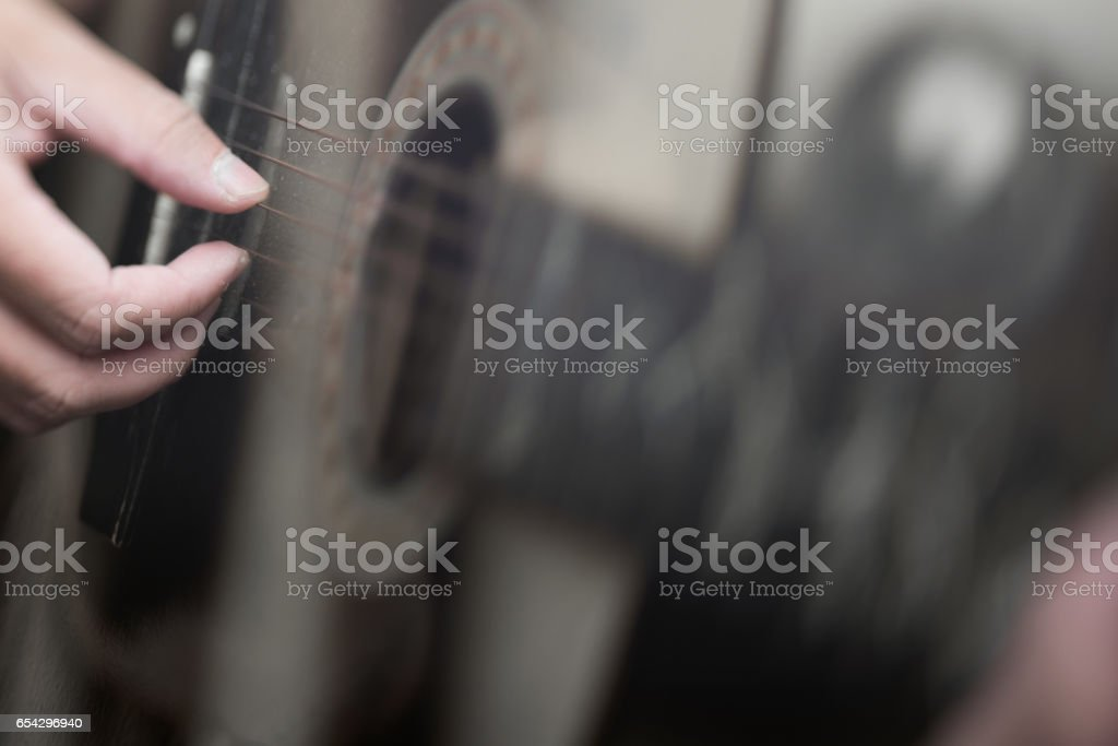 Hand playing on acoustic guitar stock photo