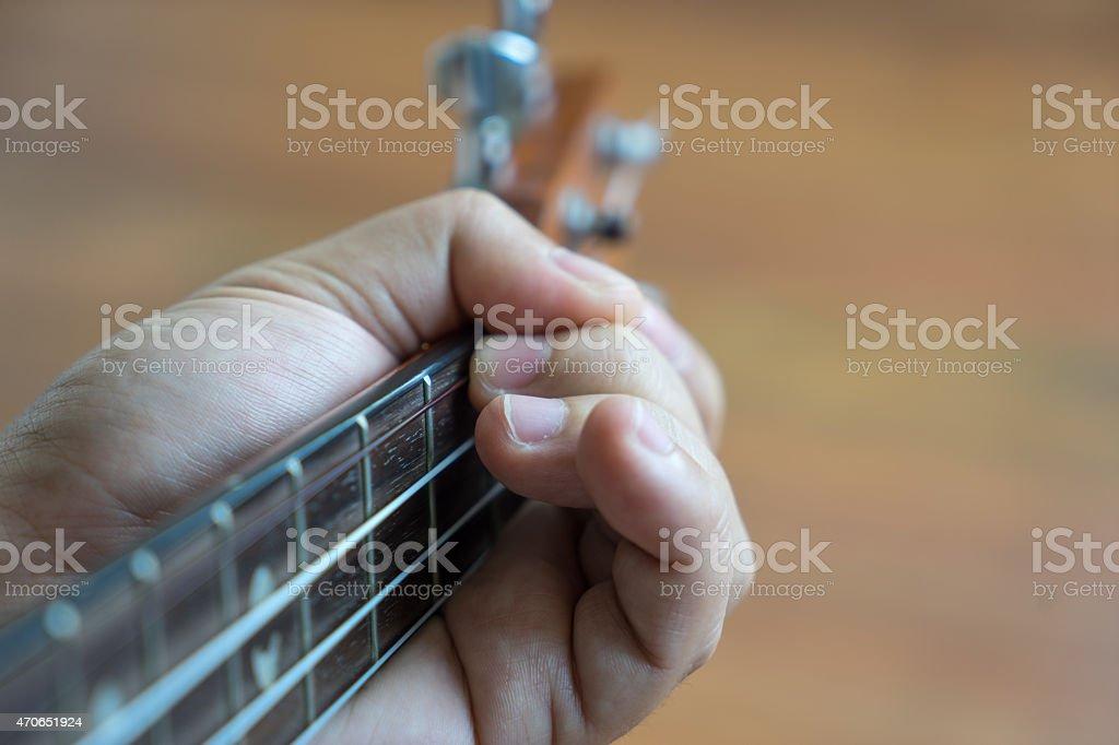 Hand playing ukulele, Close-up stock photo