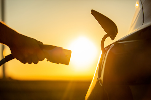 Close up of hand plugging electric charger to socket in electric car at sunrise