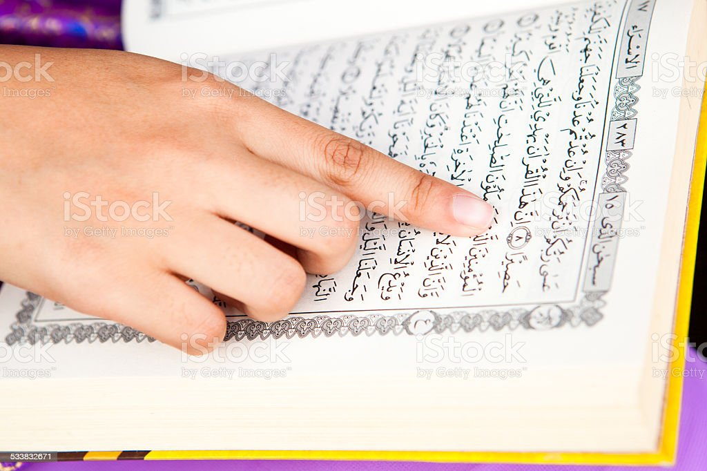 Hand pointing and reading islamic koran stock photo